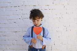 Young boy holding paper heart, looking down