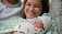 "Woman holding newborn baby in delivery room. ""Top 5 Questions About Epidurals Answered"" [BLOG]"