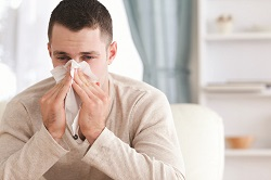 Man with flu blowing his nose. Most Common Flu Shot Questions blog