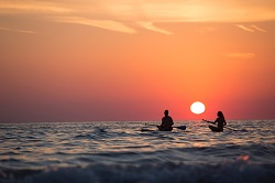 couple canoeing at sunset: tips to vacation mindfully