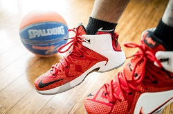 Basketball and pair of feet in athletic shoes