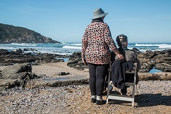 Older woman on beach in wheelchair with caregiver