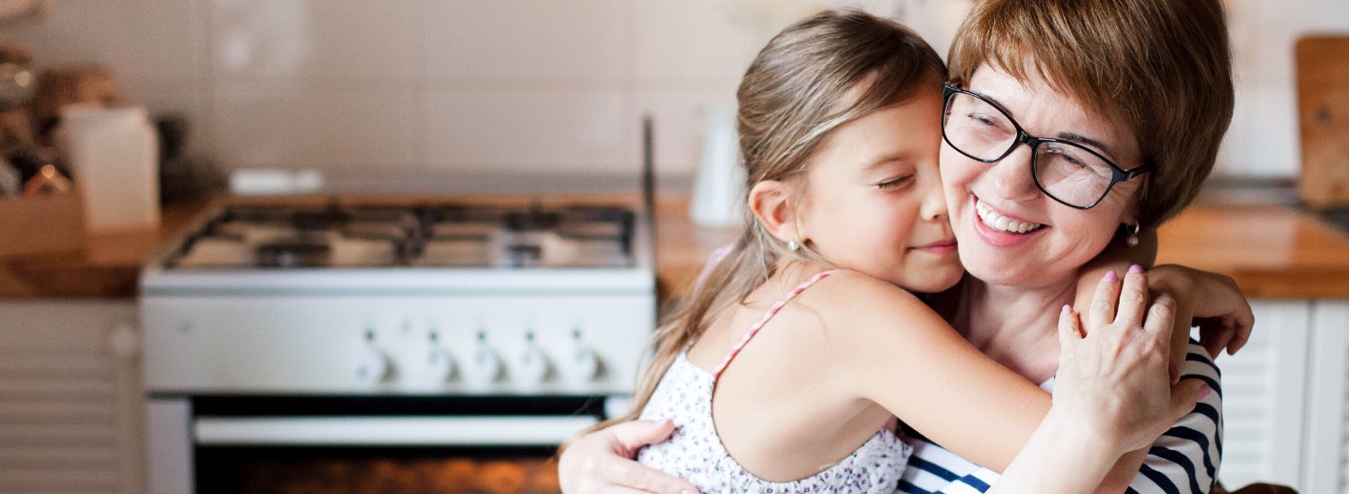 daughter hugging mother in kitchen