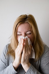 Woman Blowing Nose. Blog: More Flu Questions, Answered